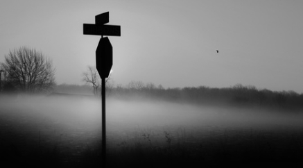 The Crossroads. Country crossroads shrouded in with stop sign silhouette shrouded in fog.