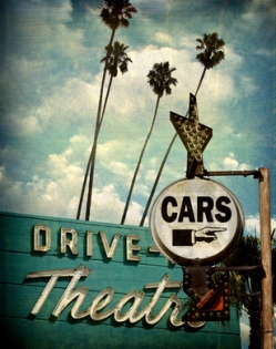 aged and worn vintage photo of drive theater and cars sign with pointing hand