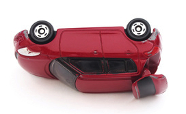 miniature red toy car in accident on white background