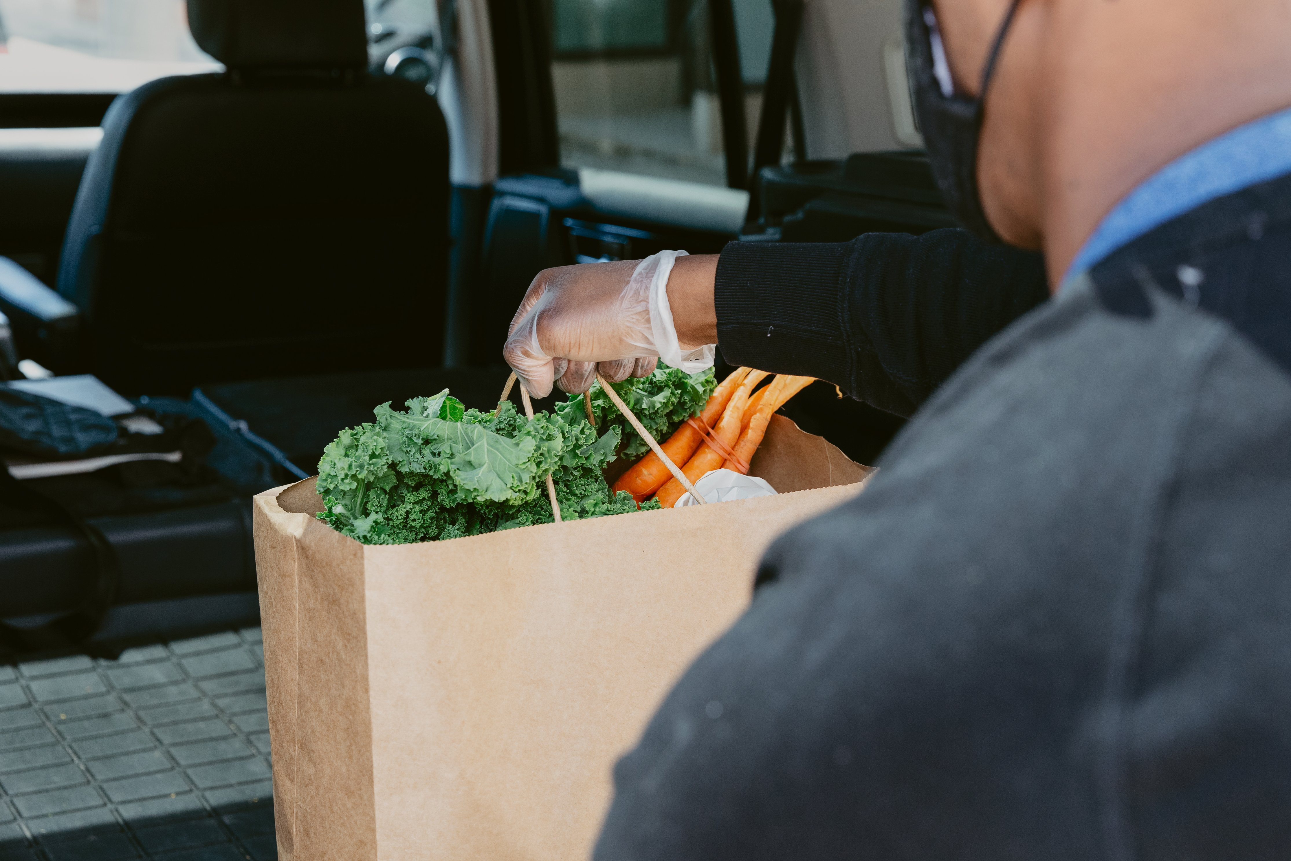 close-up-of-man-placing-groceries-in-back-of-car